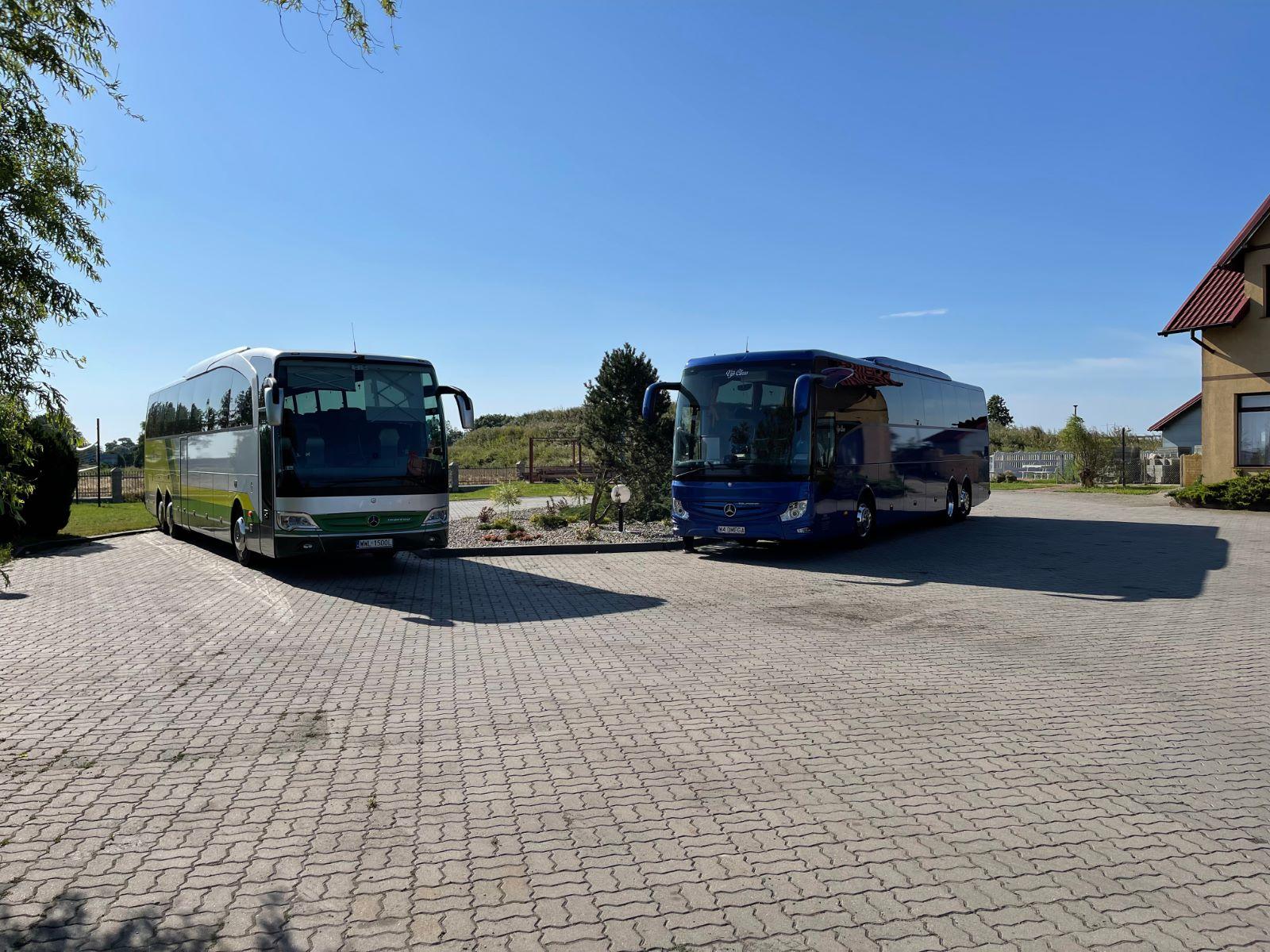 Dwa autokary tyrystyczne na parkingu oczekujące na grupę seniorów nad morzem